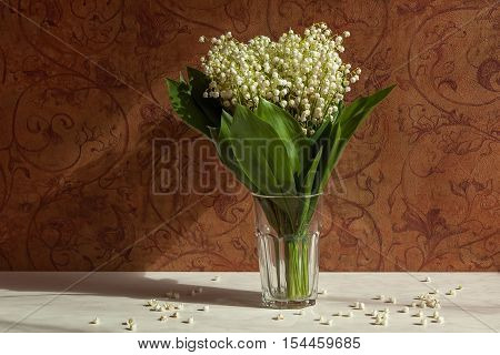 Vase with lilies of the valley. Vase with lilies of the valley on a background of brown wall with floral pattern.
