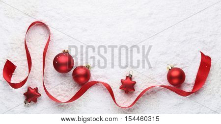 Red balls and ribbon on snow