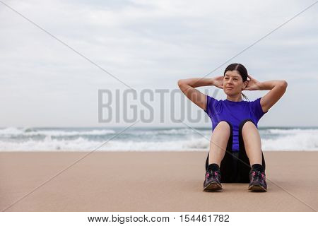Female athlete executing situps at the beach on an Autumn day.