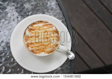 hot fresh coffee in white cup with caramel sauce foam on glass table in garden on grass and rock at coffee time