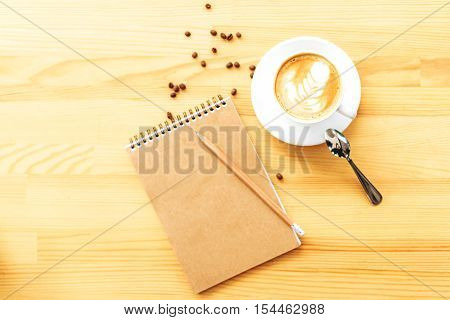 clean jotter with space for text on a wood table with art coffee