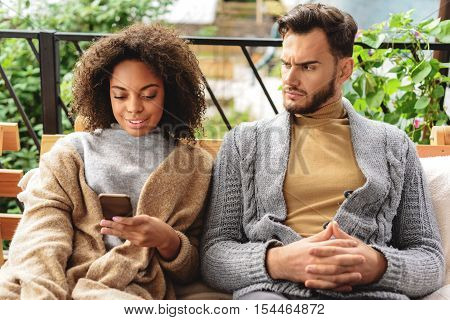 resentful man looking at his wife who ignoring him