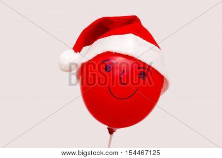 Red balloon with friendly face and Christmas bonnet on isolated against a creme background.