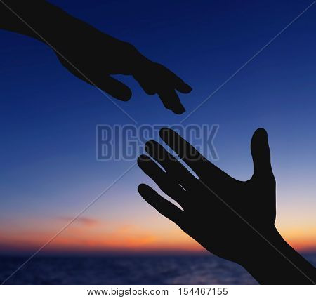 Silhouettes of female and male hands reaching to each other on sky background. Help and care concept.