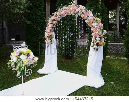 Wedding arch and a table with wineglass in the meadow