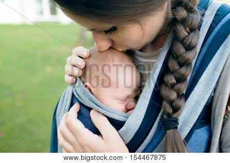 Beautiful young mother kissing her newborn baby son in sling outside in green nature.