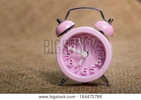 Clock Alarm set at ten to seven on jute background