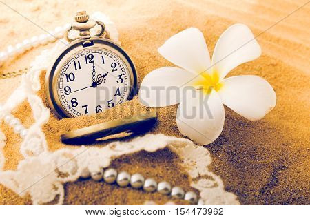 Vintage necklace watch with vintage style on the sand beach