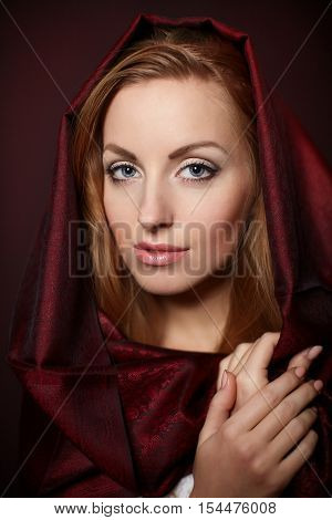 Beautiful woman closeup portrait bright makeup in red color cloth isolated on red