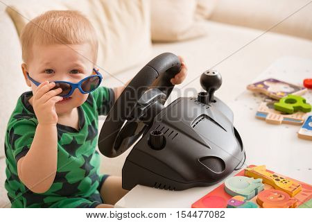 Cute adorable toddler boy sitting on the sofa and playing with computer steering wheel. Future driver. Getting ready for professional driving. Child driving a car. Funny boy indoors. Boy and a car.
