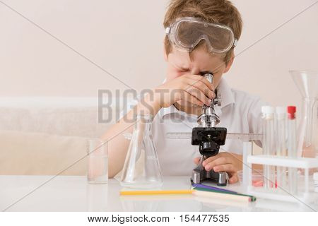 Cute elementary schoolboy looking into microscope at his desk at home. Young scientist making experiments in his home laboratory. Indoors. Child and science. Education concept.