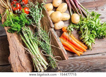 Fresh vegetables on bark on old wooden table