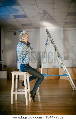Girl And Construction Ladder. Studio Shot Of A Young Woman With A Construction Ladder In The Room