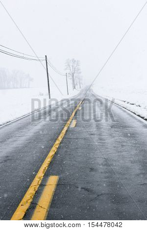Empty Highway During Winter Snow Storm and Telephone Lines