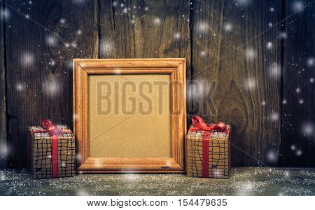 Photo frame with two boxes tied with red ribbon on a wooden background.
