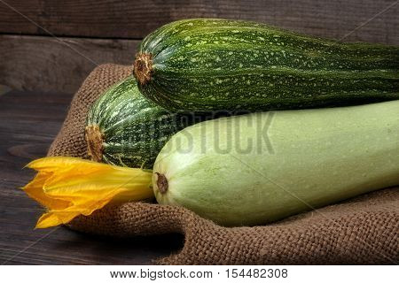 green zucchini and courgettes with a flower on sackcloth and wooden background.