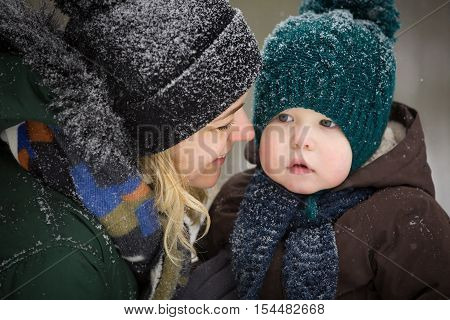 Portrait of young mother and little toddler boy in the winter forest. Family enjoying winter. Child and woman watching falling snow outdoors. Winter Christmas and lifestyle concept.