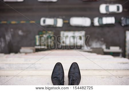Close-up of man's feet standing on the edge of the roof. Top view on man's boots on the balcony of high building. Depression and instability concept. Crisis.