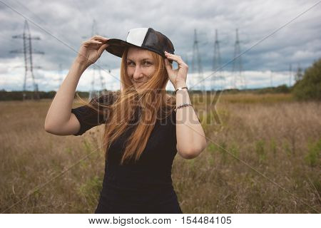 Young energy happy woman wears a cap hip-hop cap on yellow field with power pylons, cloudy autumn