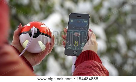 Samara, Russia - November 1, 2016: woman playing pokemon go on his iphone. pokemon go multiplayer game with elements of augmented reality. Catching the Mr. Mime pokemon.