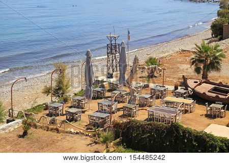 Wooden chairs and tables in outdoor greek tavern by the sea beach, Crete, Greece