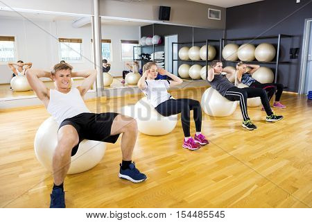 Focused team doing sit ups on bosu ball and at the fitness class. Abdominal core muscle and balance workout. Team and motivation at the gym.
