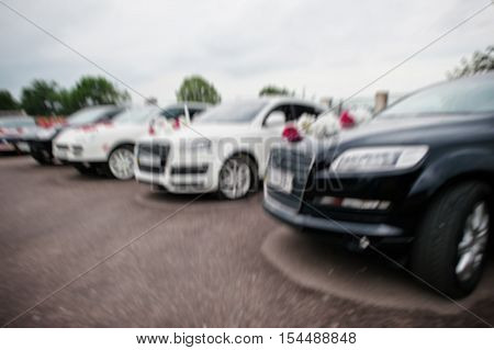 Blur effect of wedding cortege of five luxury black and white cars