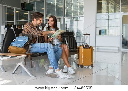 Happy young couple is sitting in airport near suitcase. They are reading map and smiling