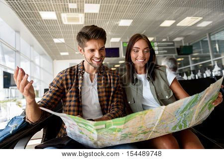 Inspired young man and woman are sitting at airport lounge and looking at map. They are laughing