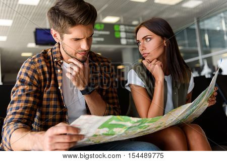 Serious young man and woman are choosing place of destination. They sitting at airport and reading map