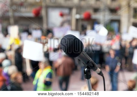 Microphone in focus against blurred protesters. Public demonstration. Protest.