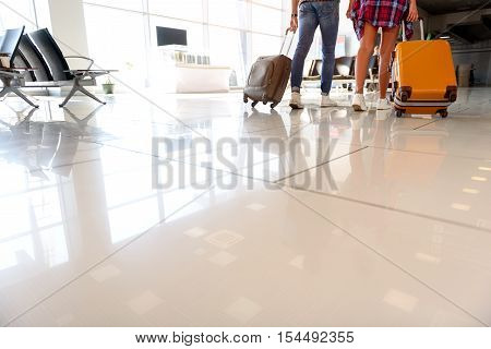 Close-up of loving couple legs going with luggage at airport. Focus on floor