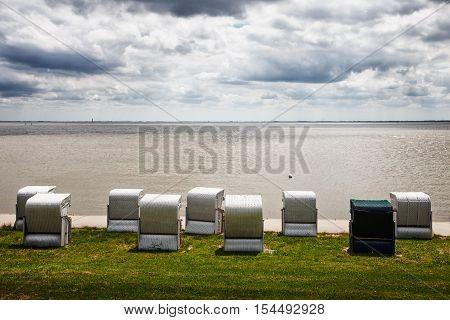 Beach chairs on the dike. North sea coast Germany