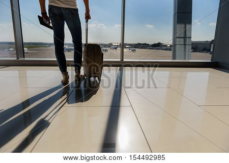 Close up of young man legs standing in airport with suitcase and ticket. He is watching planes though window