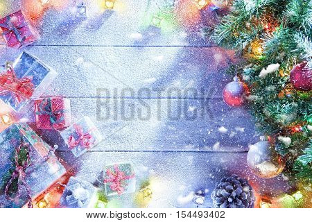 view  of lit Christmas tree  and gifts boxes  on snowbound  wooden back