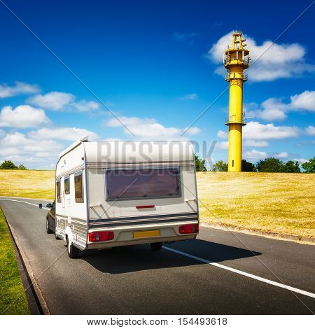 Caravan on the road. North sea landscape with yellow lighthouse on the dike. Family vacation
