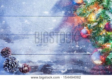 view  of lit Christmas tree  and cones on snowbound  wooden back