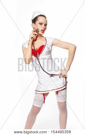 Sexy beautiful female brunette doctor with stethoscope red lingerie white stocking and red lips on a white background