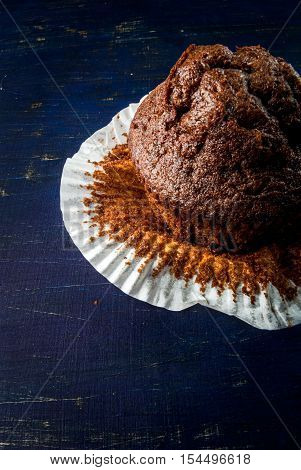 Freshly baked chocolate muffins with lemon kurd inside, on a dark blue wooden table.  Copy space, close view