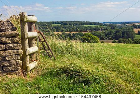 A gate and a wall with a view of the beautiful English countryside