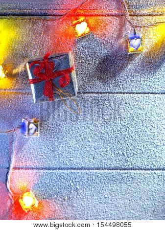 close up view  of  lit gifts box  on snowbound  wooden back