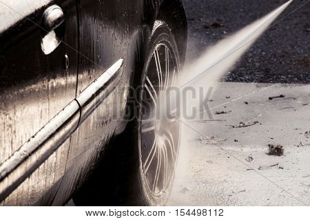 closeup of washing car with pressure washer