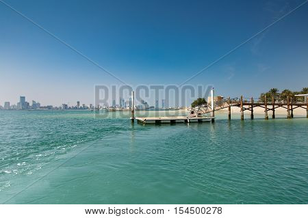 MUHARRAQ, BAHRAIN - OCT 29, 2016: Beautiful view of the boat jetty in Bu Maher Fort with the fort in the near background, Manama city in the far background and the sea in the foreground.