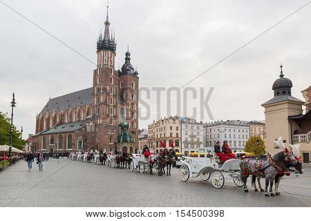 Krakow Poland - October 27 2016: Traditional horse carriages waiting in line for passengers on Krakow's main market square.