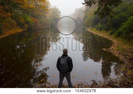 Traveler near Rakotzbruecke (Devil's bridge) in early morning mist in autumn Kromlau Germany