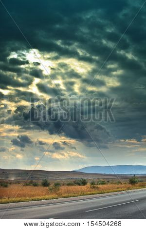 Gloomy skies. Through the dark clouds breaks sunlight. Sun rays. Dark storm clouds. The sky before the storm. Mountain in the background. Crimean plains and foothills. Landscape. Dry grass. Autumn weather. The route across the plain. vertical landscape