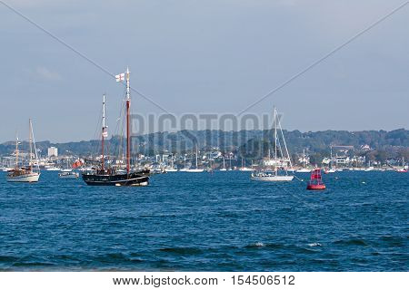 Sailing vessels and motor craft anchored in Poole Harbour Dorset England.