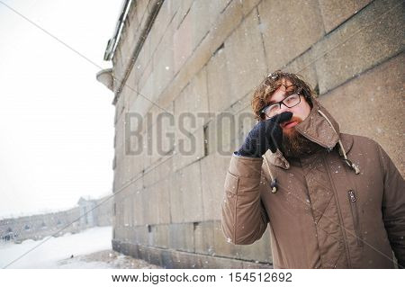A bearded young man rubs his frozen nose with your hand on a cold winter day.