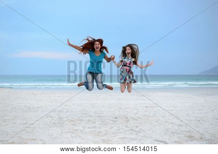 Woman and girl jumping at the beach