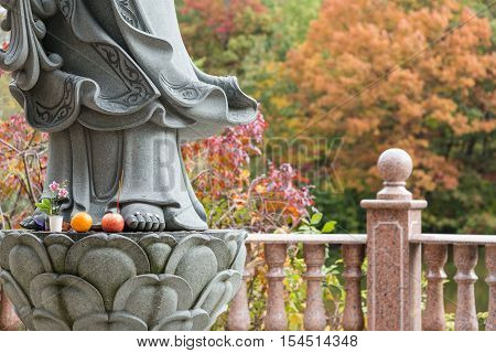 Offerings at the foot of Guanyin statue female buddha of compassion and mercy